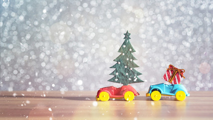 Toy Car with Christmas tree and gift box. Christmas landscape with gifts and snow. Merry christmas and happy new year greeting card with copy-space. Christmas celebration holiday background.