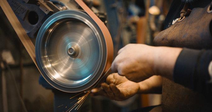 Craftsman uses a belt sander in machine shop.