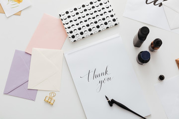Close up photo of classic ink pen and beautiful notes on white desk isolated