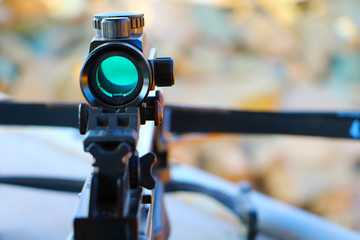 Crossbow optical sight  aiming from the first person on defocused blurred background
