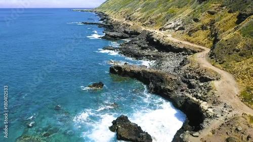 Aerial: Rugged Volcanic Coastal Reef, Blue Ocean, Blue Sky