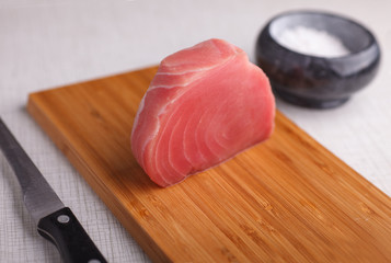 raw uncooked tuna steak on cutting board near knife, salt