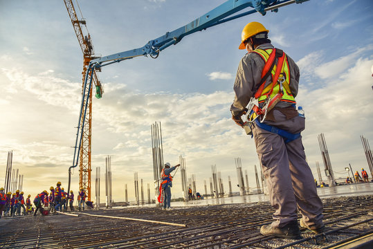A construction worker control a pouring concrete pump on construction site and sunset background