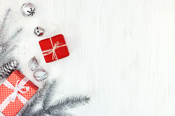 silver christmas tree branch, decorations, nuts and gift boxes  on white wooden background with copy space