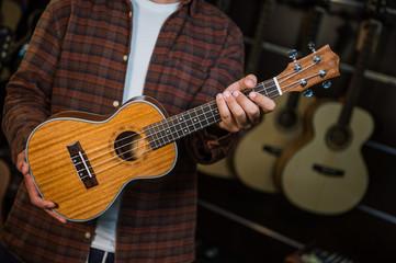 Happy teenage boy choosing best acoustic guitar in musical shop