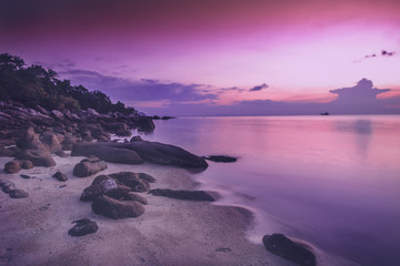 beautiful bright purple pink sunset by the sea, stones on the sand. Stunning scenery