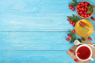 tea with rose hips and honey on blue wooden background with copy space for your text. Top view