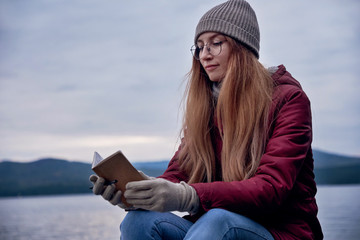 Young hipster woman getting inspiration at the lake shore on sunset