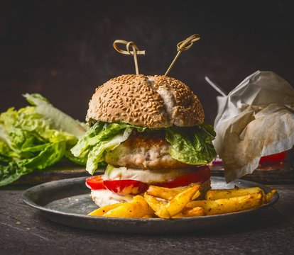 Homemade burger on dark rustic wooden background with French fries , front view, close up. Fast food and snack concept