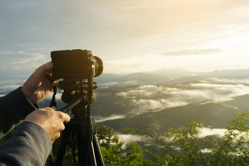 The man hand holding Mirrorless camera put on the tripod for recording the viedo or capturing the beautiful mountain scenery with sun light in th morning.