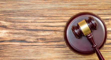 Wooden gavel with stand on wooden table. Top view. Justice concept.