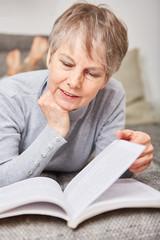 Frau als Senior liest neugierig ein Buch