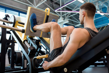 Rear view of muscular sportsman doing leg exercises using machine in modern gym
