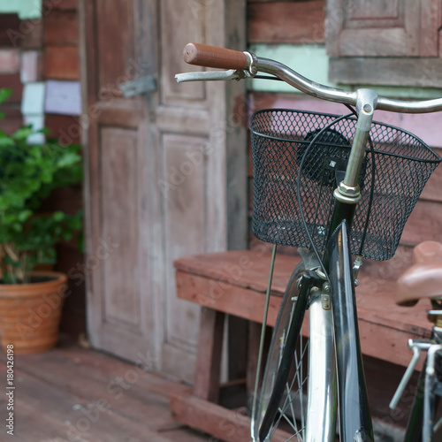 70ee6c93ef8 go home with blue vintage old black and brown bicycle or bike at front of  retro wooden home terrace with wood door and window with tree in flowerpot  for ...