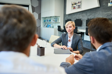 Portrait of young successful businesswoman talking to partners sitting at meeting table in board room presenting project