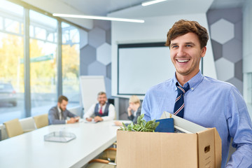 Portrait of happy young man holding box of personal belongings being hired to work in business company, copy space