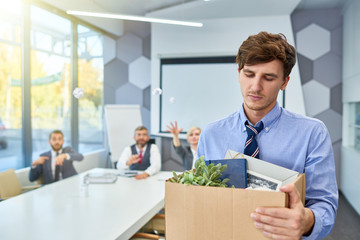 Portrait of sad young man holding box of personal belongings being fired from work in business company, copy space