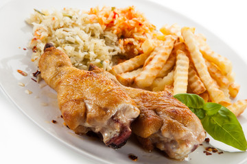 Grilled drumsticks with french fries and vegetables on white background