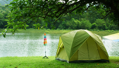 nature landscape green camping tent with colorful umbrella under the tree and blue with yellow tarp on meadow with lake or river and tree mountain for holiday relax on winter and gray sky at ched khot