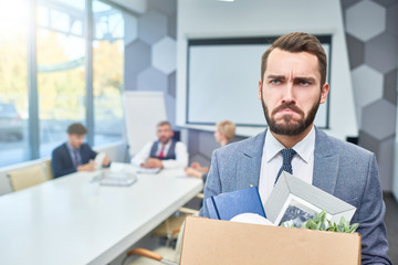 Portrait of sad bearded businessman holding box of personal belongings being fired from work in company, copy space