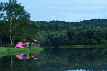 nature landscape pink camping tent and blue with yellow tarp on meadow with lake or river and tree mountain for holiday relax on rainy season and blue with gray sky and water reflection at ched khot