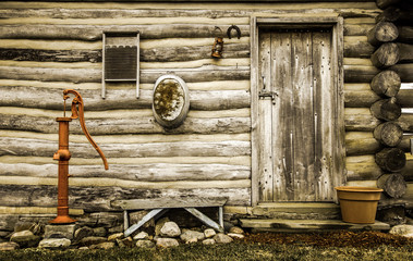 Rustic Log Cabin Exterior. Front door and exterior wall of a historical rustic log cabin with antique décor.