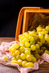 Picture of wooden basket with green grapes on table