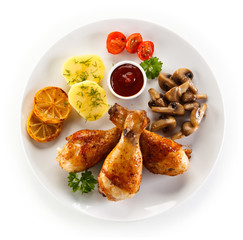Grilled chicken drumsticks with vegetables on white background