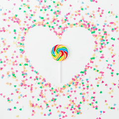 Heart symbol made of colorful bright confetti and candy on white background. Flat lay, top view copy space. Love concept