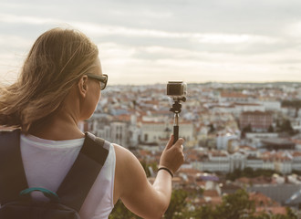 Woman traveller with camera shooting video.