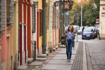 Woman traveler with a backpack and phone walks along the street of an ancient European city