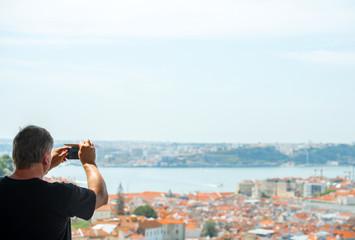 Senior man taking photos of old town.