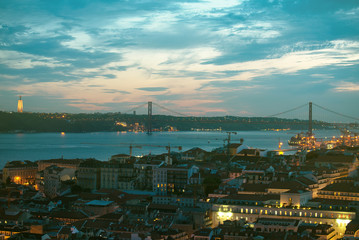Alfama downtown and the 25 April Bridge in Lisbon at evening.