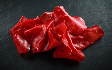 italian air-dried salted bresaola beef thinly sliced and served on stone board. Perfect appetizer