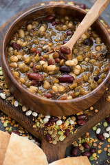 Close-up of a wooden bowl with thick bean soup, selective focus, vertical shot