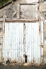 casa en ruina antigua con puerta de madera rota y en ruruida con aspecto pobre y deteriorada por los años