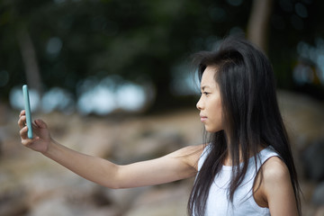 Attractive brunette Asian female with slim arms holding electronic device and taking self portrait while spending vacations in beautiful place by the sea. People, lifestyle, technology and travel