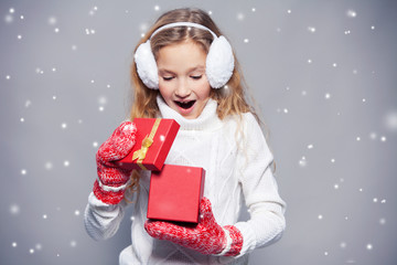 Girl in winter clothes with gift