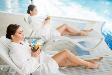 Idyllic scene of two restful girls in white bathrobes relaxing by swimming-pool on deckchairs