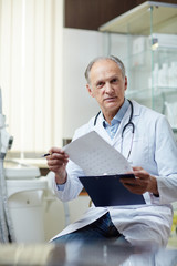 Senior practitioner in uniform looking through medical papers in clinics