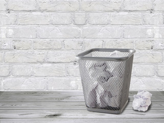 A trash can with crumpled papers stands on the floor against a white brick wall