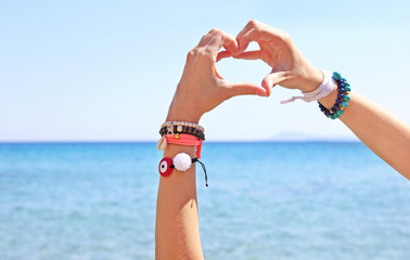 greek jewelry advertisement on the beach - heart symbol with hands