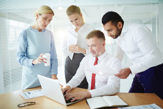 Group of business people watching teleconference in front of laptop in office