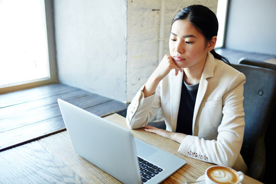 Serious young female sitting by table in cafe in front of laptop and reading data