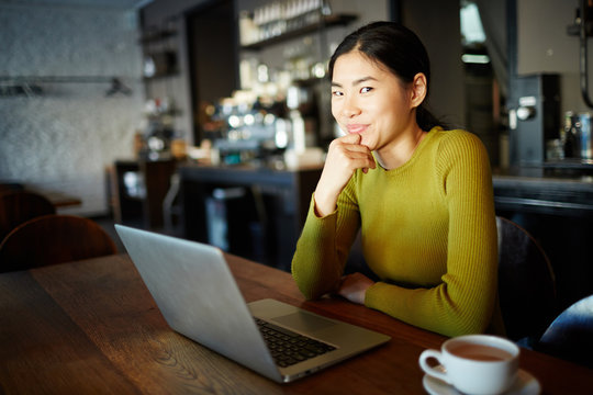 Young Asian girl with laptop watching curious video in cafe by cup of drink