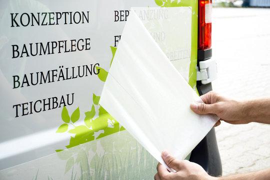 Abziehen von Übertragungspapier bei Fahrzeugbeschriftung