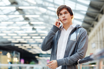 Serious guy speaking by smartphone during sale in shopping center