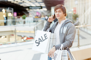 Young man with paperbags talking by smartphone after making purchases on seasonal sale