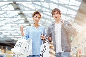 Happy young heterosexual couple with shopping bags walking down department store after sale