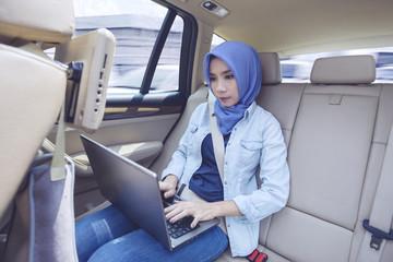 Muslim woman using laptop in car